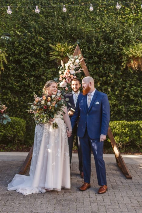 curvy bride holding hands with groom